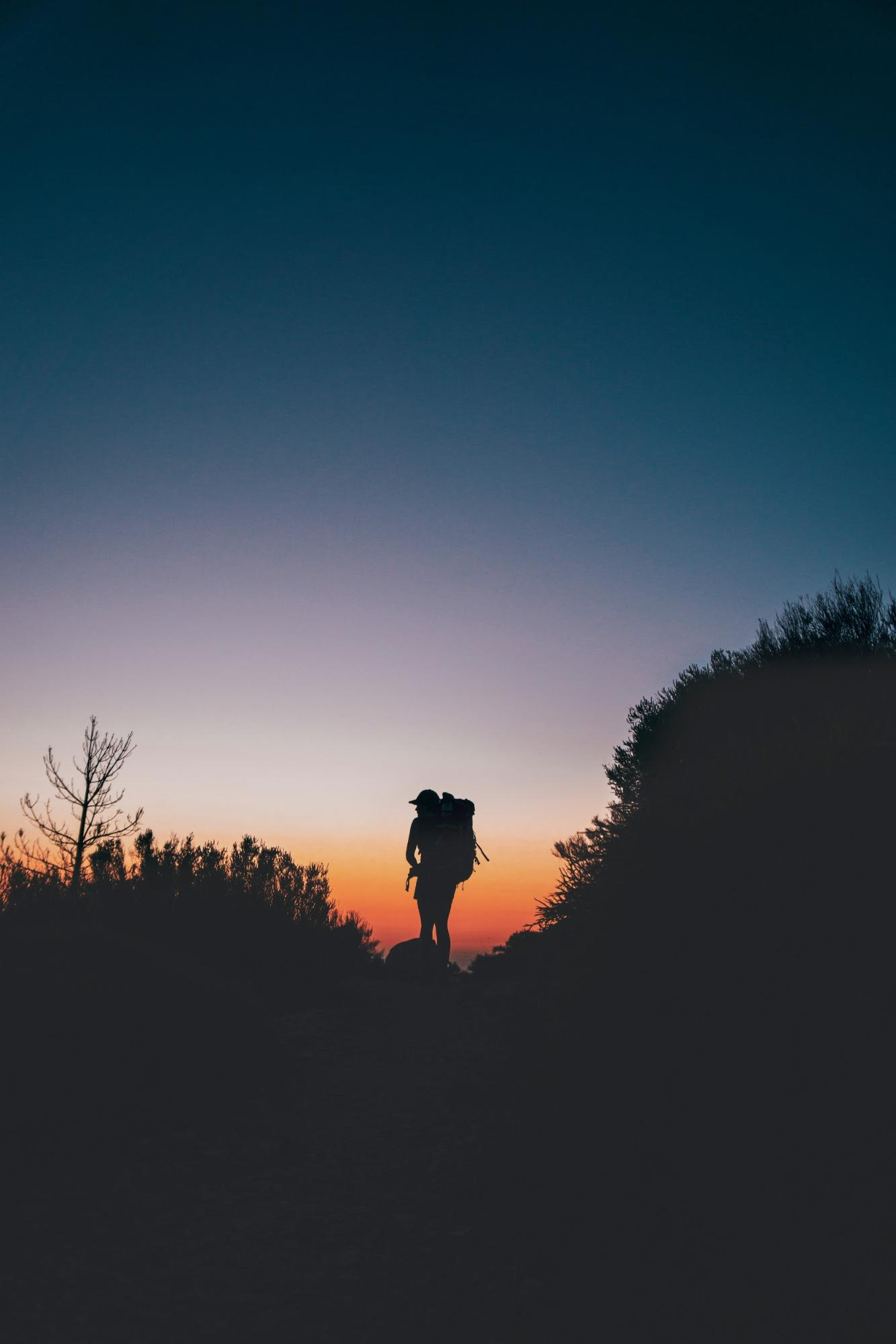 Hiker on dark landscape during sunset