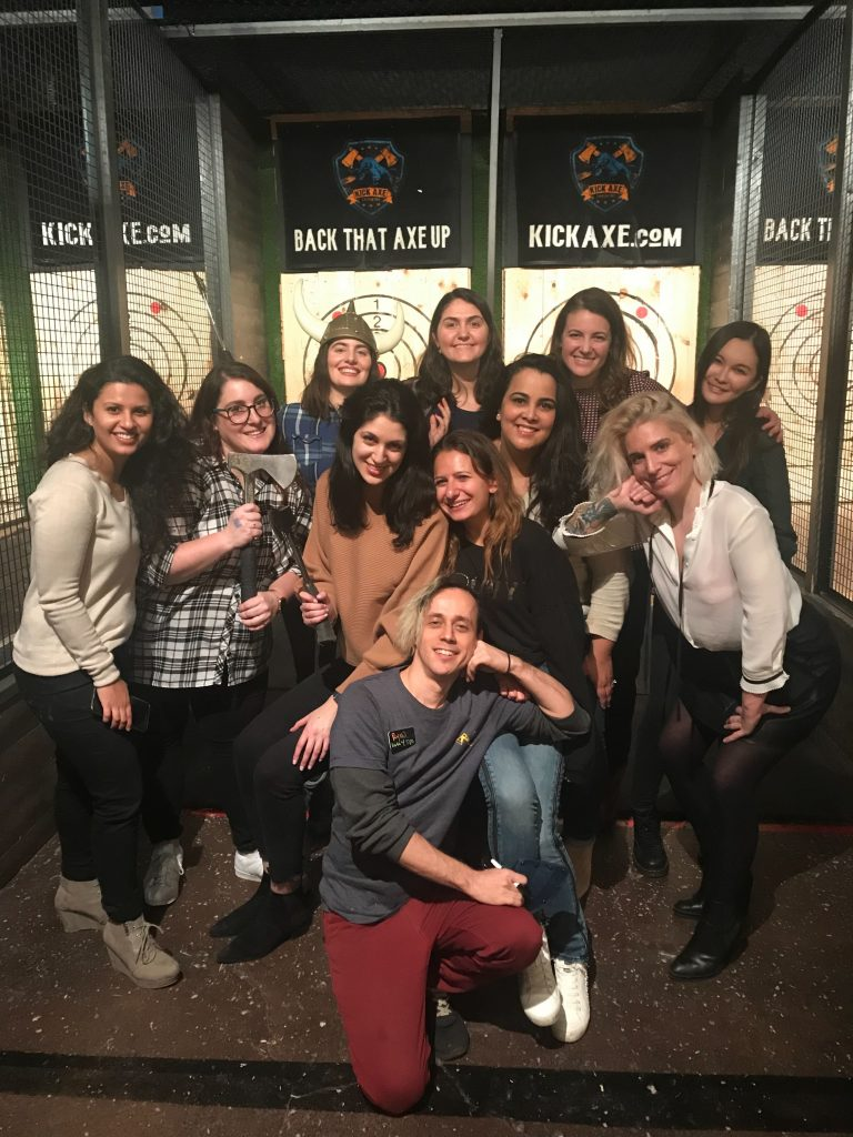 InRhythm's Women in Tech group poses in front of the throwing range at Kick Axe Throwing in Brooklyn