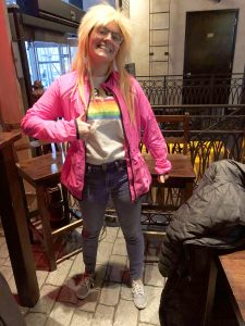 Jess in pink jacket and blonde rockstar wig